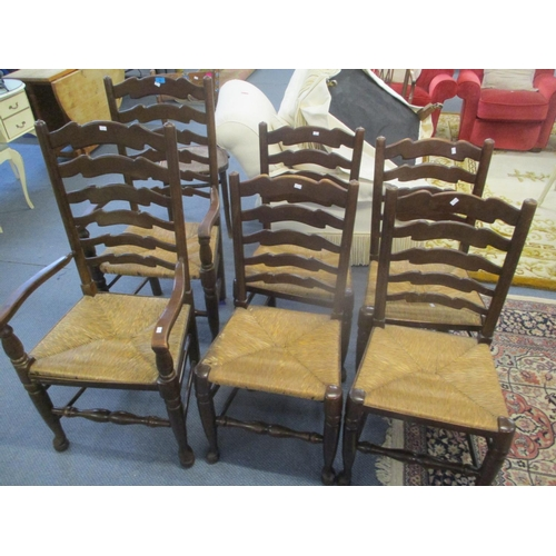 10 - A set of six oak ladder back, rush seated dining chairs, two being carvers Location: C...