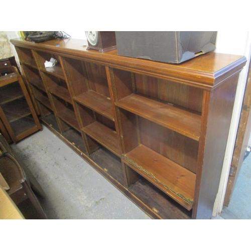 22 - A large stained pine open bookcase on a plinth base, 47 1/2