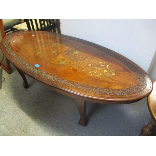 25 - A modern Indian oval topped coffee table having brass inlay, 18 1/4