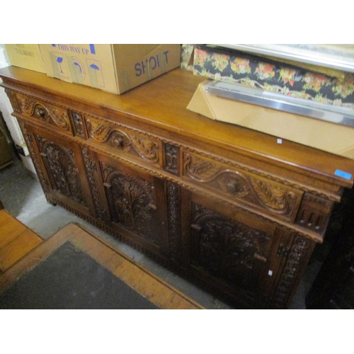 28 - A reproduction large oak carved sideboard having three drawers above three cupboards, 36