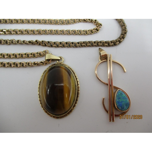 78 - A 9ct gold pendant set with tigers eye on a yellow metal chain and a 9ct gold dollar pendant Locatio...