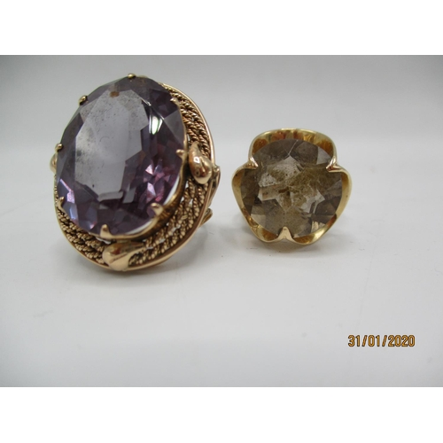 80 - Two gold coloured metal rings, one set with a purple stone and the other a citrine, 17.75g, total Lo...