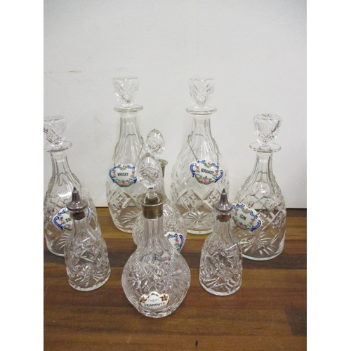 65 - A set of glass decanters and a matching pair of bottles, a pair of the small decanters having silver...