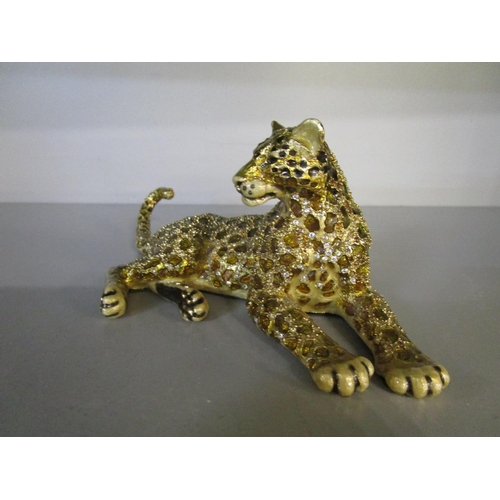 119 - Jay Strongwater b 1960, American - a metal, enamelled and jewelled reclining leopard ornament, set w...