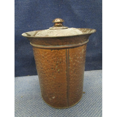 132 - An Arts & Crafts hammered copper coal bin of circular section, the domed lid decorated with two repo...