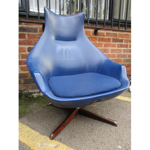 141 - Peter Hoyte - a swivel lounge chair and matching footstool in blue vinyl, chrome and rosewood, circa...