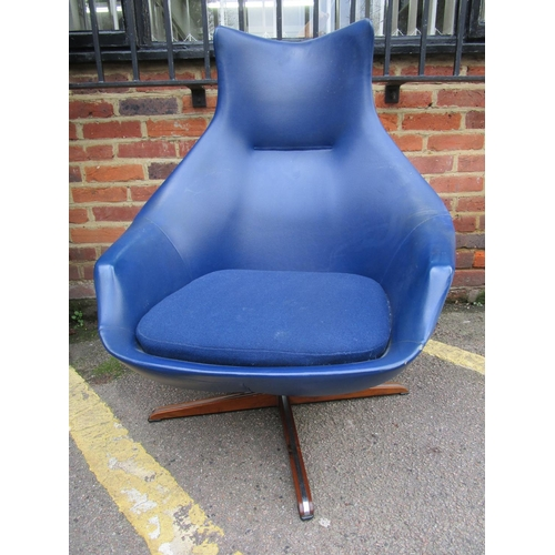 142 - Peter Hoyte - a swivel lounge chair and matching footstool in blue vinyl, chrome and rosewood circa ...