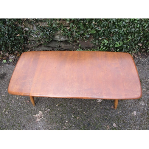 144 - An Ercol mid century style coffee table in light beech and ash, with magazine rack undertier and ell...