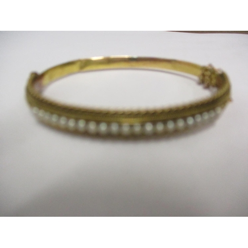 7 - A 15ct gold bangle with safety chain and a row of seed pearls, total weight 10.75g Location: CAB...