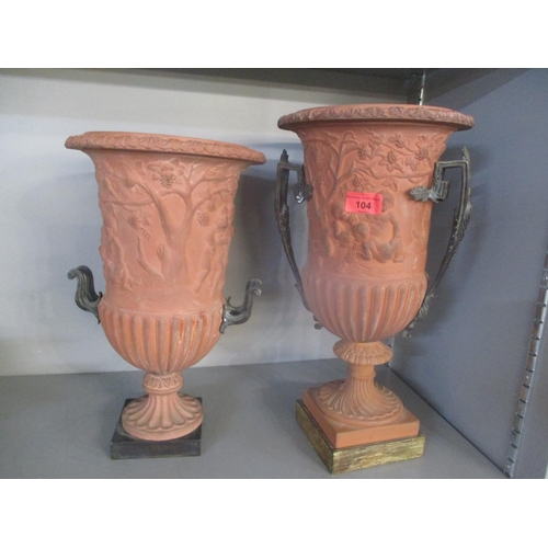 104 - Two terracotta urns with cherub ornament on a pedestal foot, cast brass handles and a plinth Locatio...