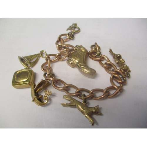 108 - A gold coloured bracelet with six charms Location: CAB...