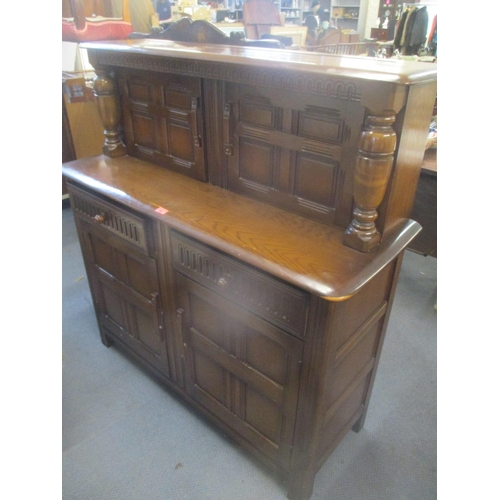 40 - A mid 20th century dark elm court cupboard having four cupboard doors and twin drawers, 49