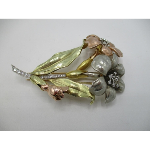 30 - A three tone gold coloured metal brooch fashioned as two flowers, the stamens and stem set with twen...