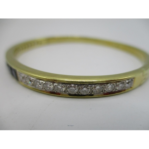 6 - A 14ct yellow gold, diamond and sapphire hinged bangle, set with twenty two brilliant cut diamonds a...