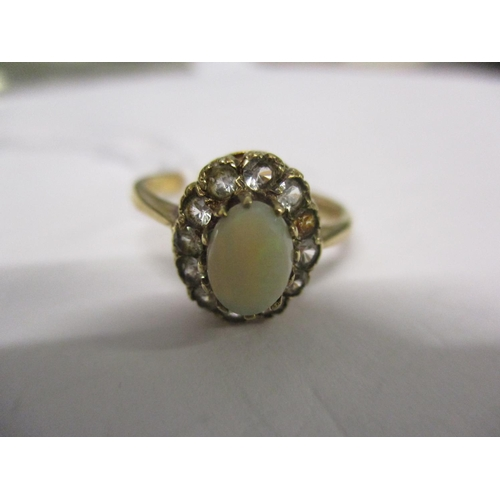 4 - A 9ct gold, opal and diamond ring having a central opal surrounded by eleven small diamonds (one is ...