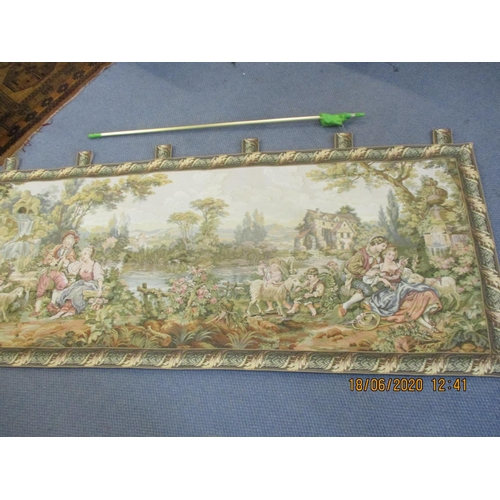 66 - A reproduction machine made wall tapestry depicting a continental scene with lovers in the foregroun...