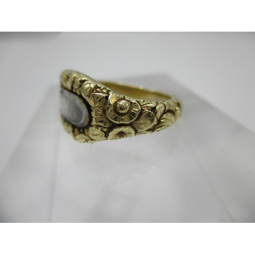 43 - A George III period gold coloured mourning ring with glazed compartment of pleated hair with flower ...