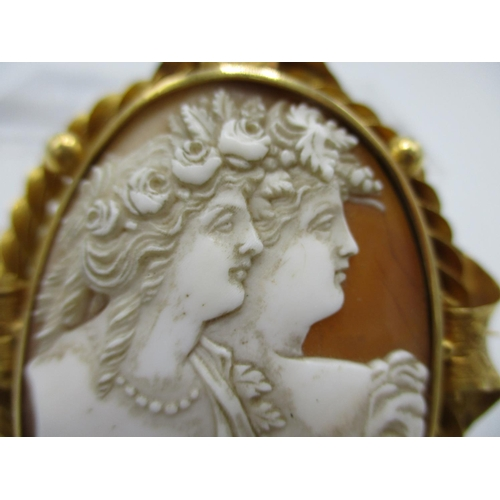 48 - A Victorian yellow metal framed cameo brooch with oval shell cameo depicting two maidens with ornate...