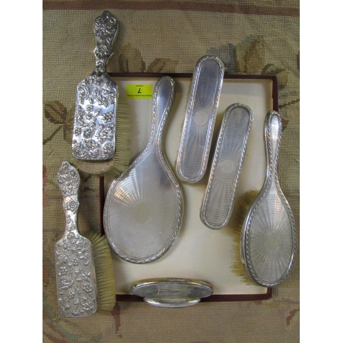 7 - A silver backed four-piece dressing table brush set with mirror, and two other dressing table brushe...