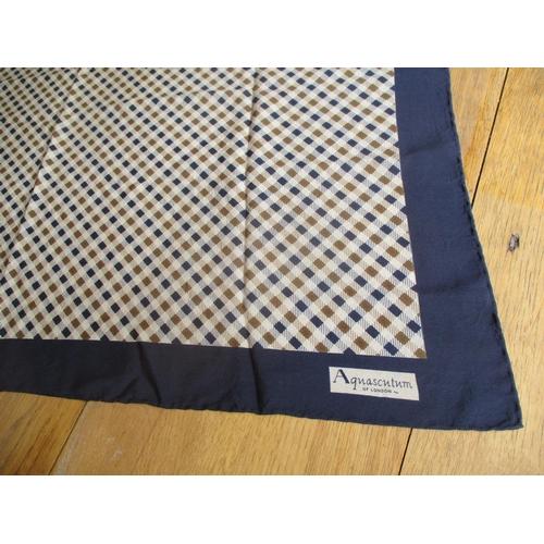 10 - Aquascutum - a late 20th century silk scarf having a navy border enclosing a navy and tan chequered ...