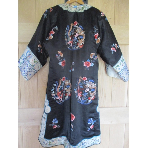 15 - A Chinese black silk coat, late 19th/early 20th century having cream bordered cuffs and hems, hand e...