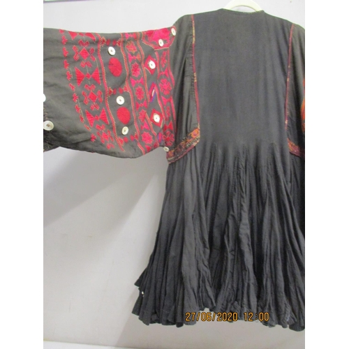 24 - An early 20th century Afghan tribal costume in red and black decorated with mother of pearl, pearliz...