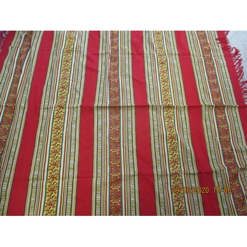 4 - A mid to late 20th century Eastern throw in rich red and gold colours having a fringe...