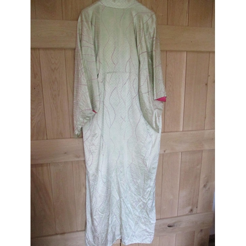 23 - A 20th century pale green silk kimono with a cream lining having a fuchsia coloured edge, measuremen...