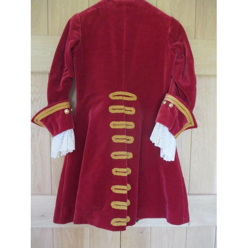 38 - A theatrical red velvet coachman's jacket with gold coloured brocade and buttons, having cream lace ...
