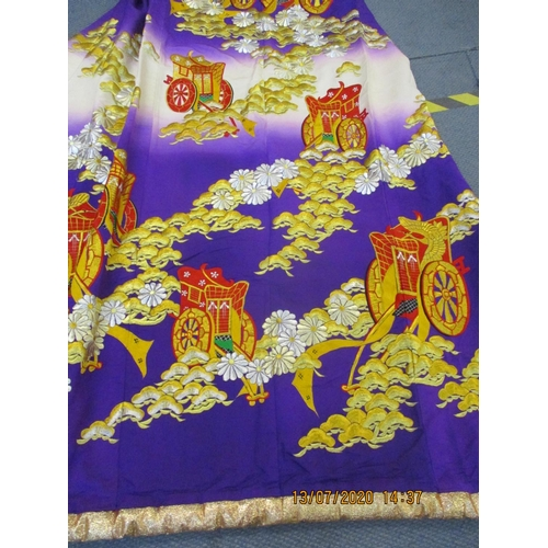 21 - A heavily embroidered Japanese kimono having a purple ground with gold and silver thread, floral det...