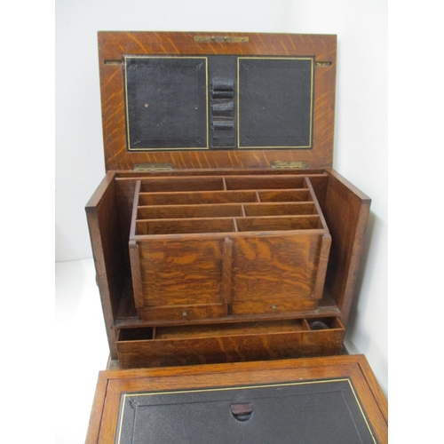 292 - An early 20th Century oak writing slope with a compartmented interior, two drawers and a folding scr...