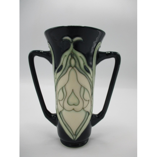 304 - A Moorcroft snowdrop pattern MCC collectors vase of flared form with twin handles, in green and blue...