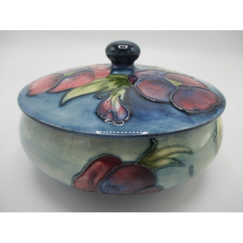 309 - A Moorcroft pansy pattern lidded powder bowl, decorated in purple, green and blue with impressed fac...