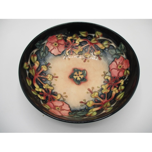 315 - A Moorcroft Oberon pattern bowl decorated in pink, yellow, purple and green, on a dark blue ground w...