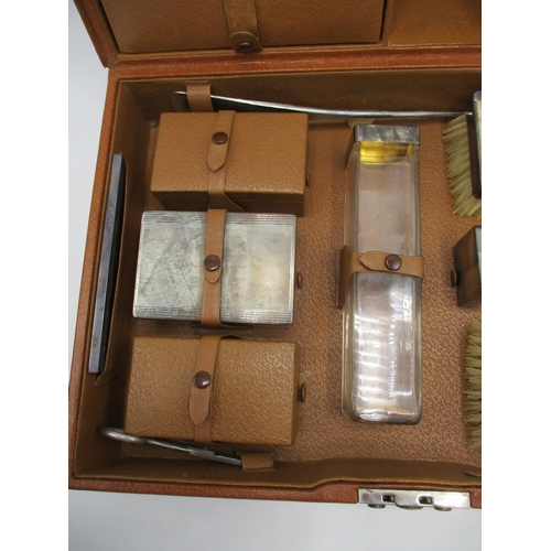 316 - A 1940s gentleman's brown leather travelling vanity case enclosing silver lidded three glass jars, a...