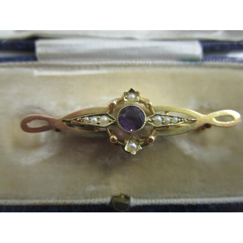 57 - A Victorian 15ct yellow gold bar brooch set with a central amethyst stone and seed pearls, total wei...