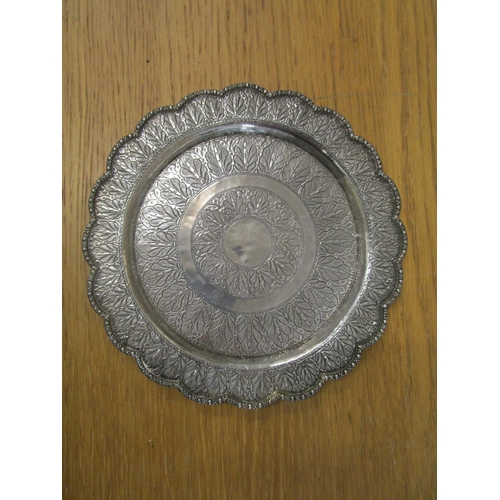 72 - An Indian white metal plate with petal shaped rim and circular bands of styalized engraved leaf deco...