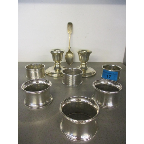17 - A pair of silver filled dwarf candle holders, a silver teaspoon and six mixed silver napkin rings, t...