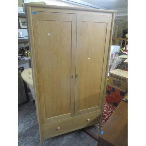 55 - A modern light oak two door wardrobe with a single drawer below 76 3/4 H x 44 1/2 W Location: G...
