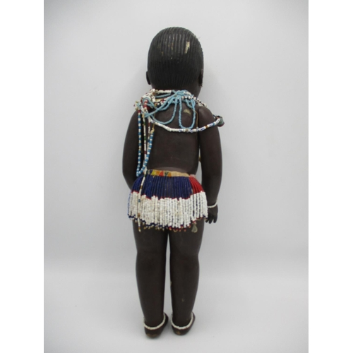 226 - An Anglo African carved wooden doll with painted features, mobile limbs coloured glass bead necklace...