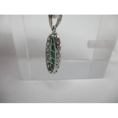 232 - An 18ct white gold Art Deco style pendant set with a column of emeralds within a band of diamonds, 2...