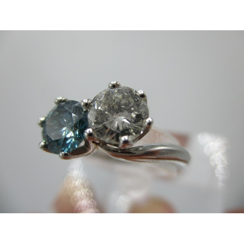 234 - A platinum ring set with a round cut diamond 0.71ct and a round cut fancy vivid blue diamond, approx...