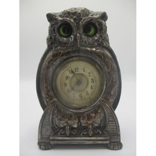 24 - An early 20th century Arts & Crafts silver plated fronted mantle clock modelled as an owl with autom...