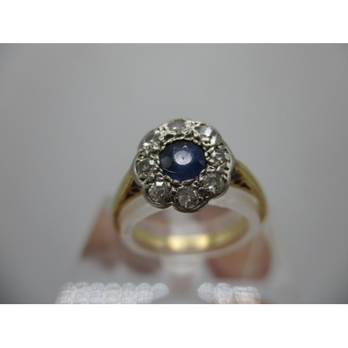 240 - A gold and platinum coloured ring set with a central blue sapphire, set within a band of eight diamo...