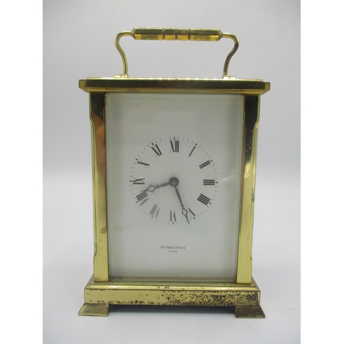 25 - A late 10th century brass ceased carriage clock, the white enamel dial having Roman numerals and sig...