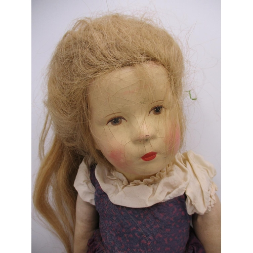 256 - A German painted faced and cloth body doll with blond hair and a purple dress, 20