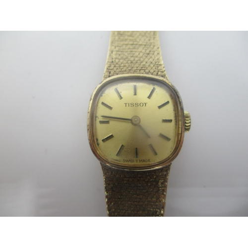 3 - A Tissot ladies 9ct gold manual wind wristwatch having a gilt dial with baton markers, integral fitt...