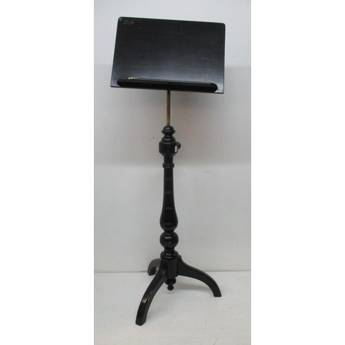 228 - A Victorian ebonized music stand with an angle adjustable panel over a height adjustable brass colum...