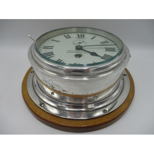 55 - An early 20th century ships clock having a white dial with Roman numerals, the dial inscribed John L...