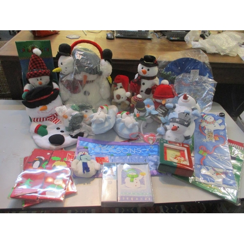 137 - A mixed lot of Christmas items to include snowman soft toys, ear muffs and slippers, together with g...